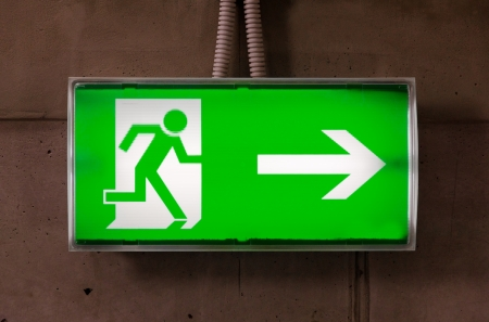 Green emergency exit sign on the concrete wall