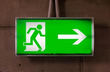 Groene nooduitgang teken op de betonnen muur Stockfoto