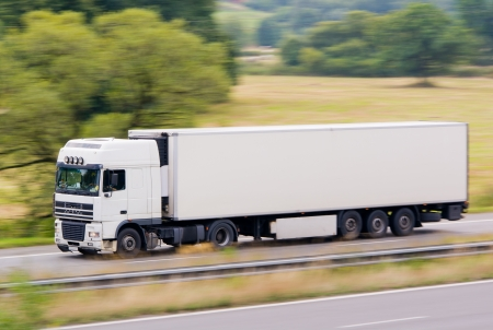 Very fast driving white truck with trailer delivering goods