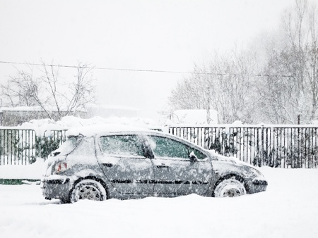 Snowy silver car parked in heavy blizzard photo