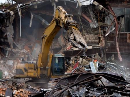 Demolición del edificio viejo por una excavadora amarilla Foto de archivo