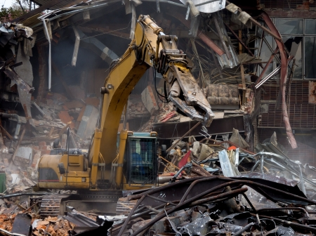 Demolition of old building by a yellow excavator Stock Photo