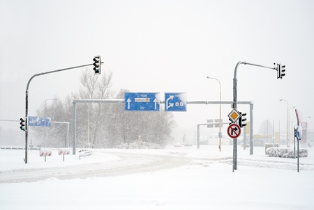 Empty winter road with traffic signs in snow calamity photo