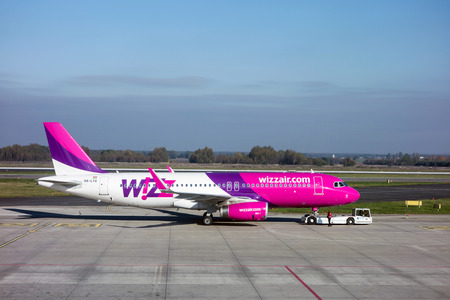 towed: KATOWICE, POLAND - OCTOBER 25: Airbus A320-232 aircraft of Wizzair airlines company towed by the service truck on Katowice Airport, Poland on September 25, 2014.