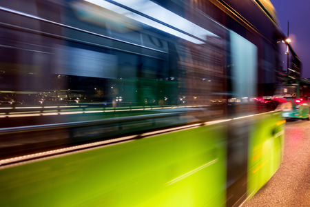 Fast driving green bus in the night city