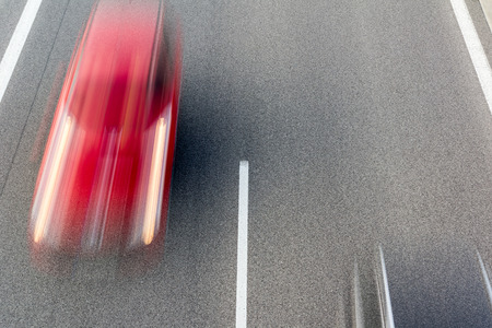 Red speeding car blurred on a highway Stock Photo