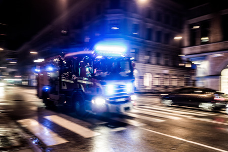 Fast driving fire truck in a night city