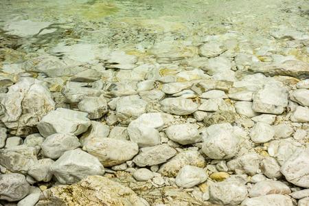 circular blue water ripple: Round stones in a small glacier lake in Slovenia Stock Photo