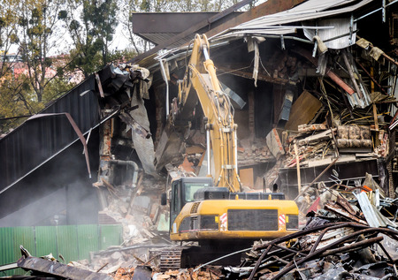 demolishing: Demolition of old building by a yellow excavator Stock Photo