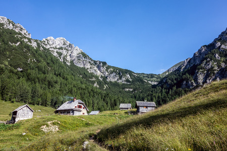 chalets: Slovenian landscape with wooden chalets, ecological agriculture Stock Photo