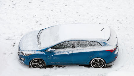 Modern blue car covered by snow in winter season