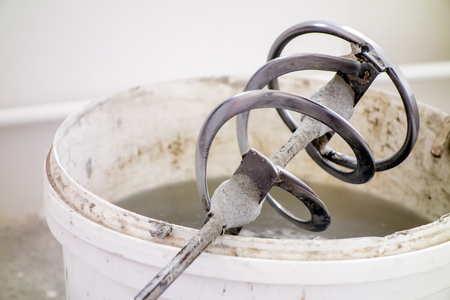 Stucco mixer laid on a white bucket ready to mix a mixture Stock Photo