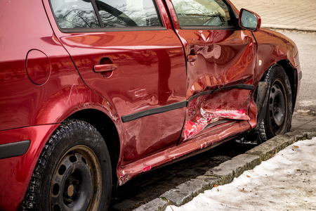 Wine red damaged car with dents after a traffic accident to its right side