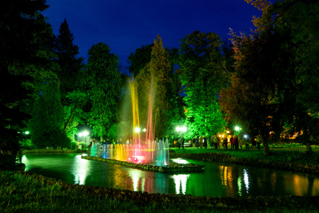 Beutiful colourful waterworks during night in Polanica-Zdrój in Poland reflected in a small lake with long exposure time and motion blur effect