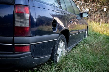 Rear view of an abandoned dark blue station wagon car in a grass Foto de archivo - 114562506
