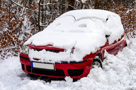 Small red car covered by melting snow in late winter or early spring Stock fotó