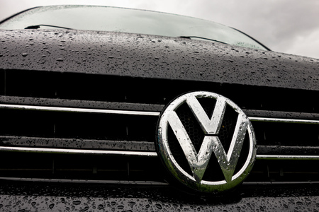 KINSARVIK, NORWAY - AUGUST 13, 2016: Logo of the Volkswagen automotive company on a black Transporter van during the raining weather with water drops