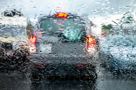 The car in a reverse gear braking and paying attention when parking to prevent an accident in a bad rainy weather viewed through a wet windscreen with blur effect.