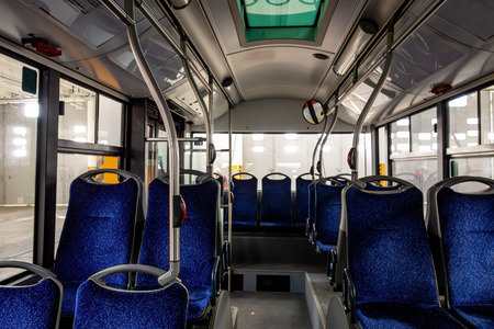 Interior of a modern city bus with blue comfortable seats and windows