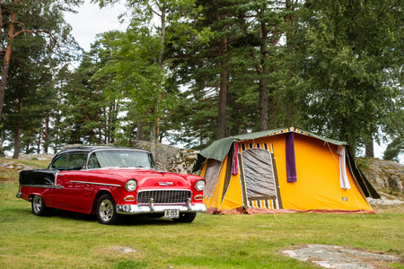 HALDEN, NORWAY - AUGUST 18, 2016: Classical American muscle car Chevrolet BelAir in a camp with a retro tent in Halden, Norway, the city famous for a big old vehicles community.