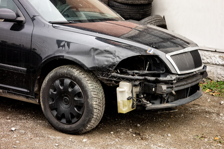 Black modern car damaged in a traffic accident without headlamps and bumper waitng to be repaired