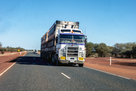 NEWMAN - WESTERN AUSTRALIA - JULY 11, 2018: The Kenworth road train truck on an asphalt road in Western Australia near Newman city. The image is taken with a strong motion blur effect. Editorial