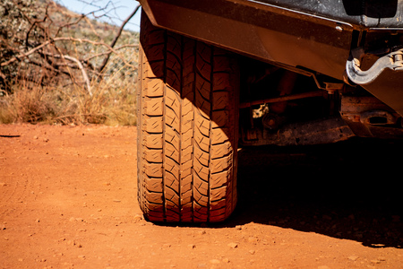 The detail of an off-road tyre on a Japanese 4x4 car. It is dirty because of a red soil and dust.