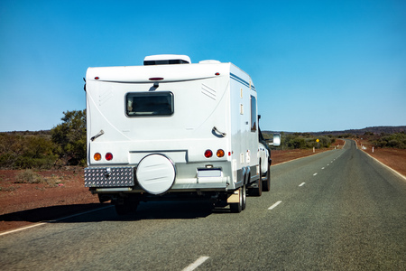 An off-road SUV car towing a caravan in Western Australia in remote outback landscape with nobody around. Stock Photo