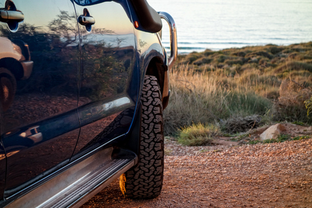 A blue modern SUV with off-road tyres parked near the ocean in Western Australia. It is on an adventurous journey. Road trips are a popular lifestyle type of vacation 版權商用圖片 - 114562337