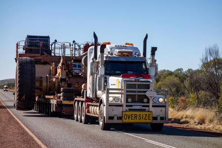 KARIJINI - WESTERN AUSTRALIA - JULY 11, 2018: The Western Star road train with Oversize sign and extremely wide dumper truck on an asphalt road in Western Australia near Karijini National Park.