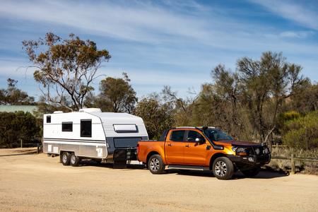 西オーストラリア州のエアインテイクと白いキャラバントレーラーを備えたオフロードピックアップカーは、冒険のために準備しました。