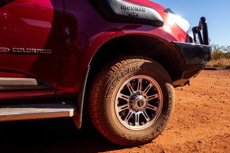 KARIJINI, WESTERN AUSTRALIA - JULY 10, 2018: The detail of a Yokohama Geolandar off-road tyre on a red 4x4 car. It is dirty because of a red soil and dust.