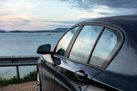 Rear view of modern luxury black car parked above the sea with a romantic view during the sunset. Relax after long hours of travelling. Фото со стока
