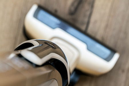 Brown portable cordless vacuum cleaner on a wooden floor for cleaning a household with a strong bokeh effect