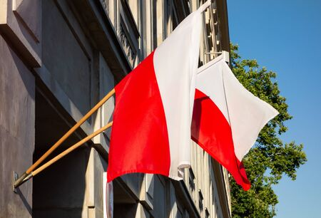 Two Polish national flags on a building in a slight breeze