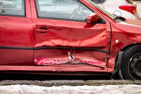 Seriously damaged side door of wine red car after dangerous traffic accident.