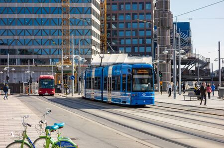 STOCKHOLM, SWEDEN - APRIL 18, 2019: Blue tram, red CNG bus and shared bicycles as an ecological mean of public transport in Scandinavia,