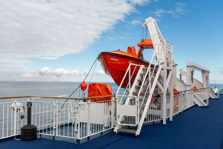 Bright orange rescue boats on a deck of a ferry to save lives