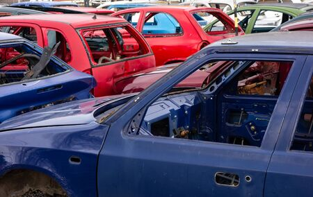A scrap yard full of car wrecks that were cleared from interior and prepared to be recycled