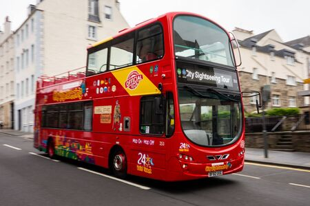 EDINBURGH, UNITED KINGDOM - JULY 29, 2019: Quickly driving Hop-on Hop-off red bus on a City Sightseeing Tour with a motion blur effect.
