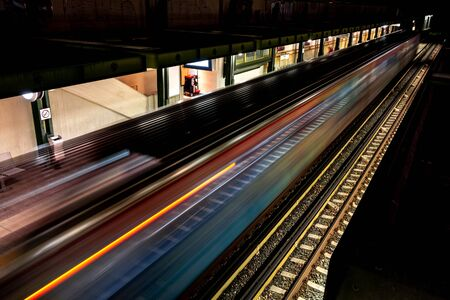 Fast driving metro train at night with light trails in Athens, Greece with a platform and railroad Фото со стока