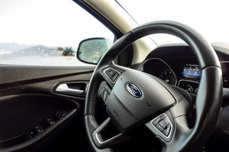 GREECE - FEBRUARY 6, 2019: A steering wheel of a modern Ford Focus car prepared to travel around the country with bokeh effect Editöryel