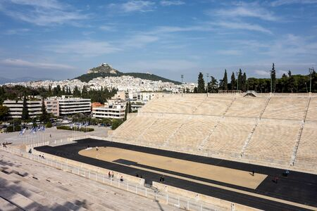 ATHENS, GREECE - FEBRUARY 5, 2019: The famous Kallimarmaro (Panathenaic Stadium) where the first Olympic games were held with runners in strong perspective view.