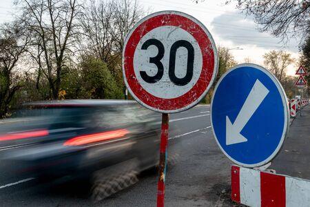 交通標識の近くでモーションブラー効果を持つ高速運転青のスピード違反車は、最大速度を30 kphまたはmphに制限します