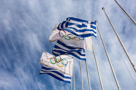 ATHENS, GREECE - FEBRUARY 5, 2019: The flags of Greece and The Olympic Games on a famous Panathenaic stadium showing the origin of this spectacular sport event