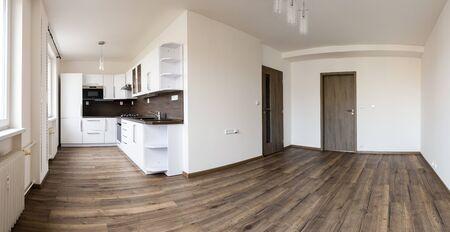 Gloednieuwe witte keuken met koffie eiken vloer en lege woonkamer na volledige reconstructie van de hele flat klaar voor het verhuizen van een nieuw gezin Stockfoto