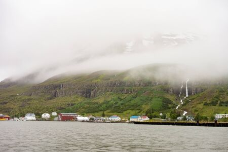 Panorama of small Seydisfjordur town in Iceland in overcast weather and mist