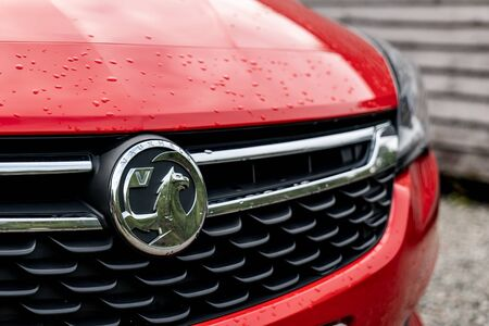 SCOTLAND - AUGUST 2, 2019: The frontal part of a red Vauxhall Astra hatchback car with a grill and badge of this auto maker