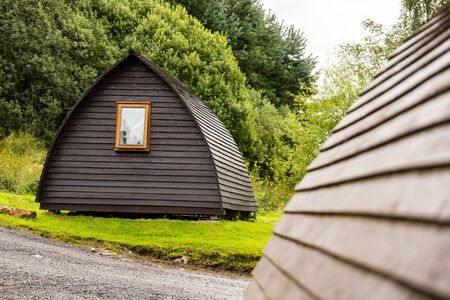 A wooden cottage (lodge) in a Scottish camp in Highlands with green grass and a blurred house in a background Stok Fotoğraf