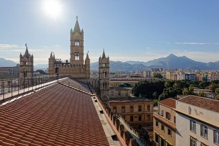 The bell tower and the roof of Palermo Cathedral with mountains at golden hour with warm light